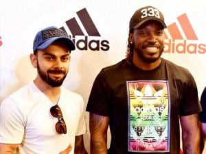 RCB Skipper Virat Kohli with teammate Chris Gayle during an event at a mall in Bengaluru