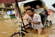 A rickshaw puller wades through a waterlogged road after a heavy downpour