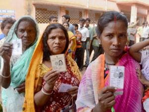 Women show their voter cards at a polling booth during the 1st phase West Bengal Assembly Elections in West Medinipur