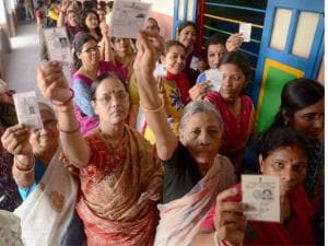 Women show their voter cards at a polling_booth during the 1st phase West Bengal Assembly Elections in West Medinipur.