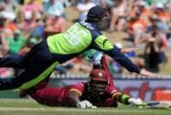 West Indies' Darren Sammy, bottom, slides into his crease as Ireland's William Porterfield leaps to field