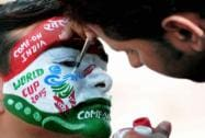 Cricket fan gets his face painted to wish good luck to team India