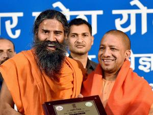 Uttar Pradesh Chief Minister Yogi Aditiyanath is presented with a memento by Swami Ramdev during Yog Mahotsav