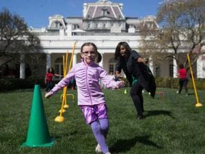 First lady Michelle Obama cheers on children as they run through an obstacle course race in the Rose Garden of the White House in Washington