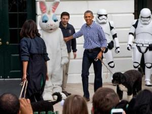 President Barack Obama and first lady Michelle Obama, with the Easter Bunny and their two dogs, Sunny, and Bo, right, walk past costumed Star Wars Storm Troopers during the White House Eraste Egg Roll