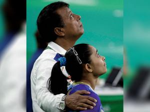 Dipa Karmakar looks at her scoreboard with her coach