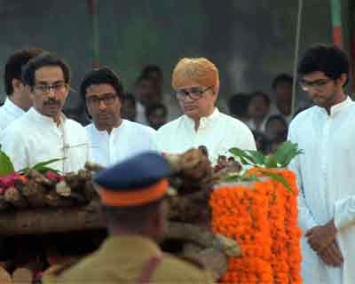 Uddhav Tahckeray (left), along with his cousin Raj Thackeray (second from left) and son Aditya (right), performs the last rites of his father, Shiv Sena party leader Bal Thackeray
