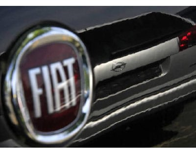 An Opel car is reflected in a Fiat car at a car seller in Darmstadt in this May 2009 file photo. Fiat is seen cutting 5,000 jobs as part of its strategic plan due to be unveiled next month, while at the same time increasing Italian production by 50 per cent. The job cuts would affect three plants in Italy and represent 15 per cent of the 30,000 workers employed on assembly lines in the country, an Italian newspaper said. <P> <b>Courtesy: Reuters</b> </P>