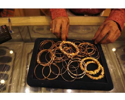 <p>A jewellery shop owner displays gold jewellery in Kolkata</p><p><b>Gold demand in India, the world's biggest buyer, was moderate on Monday after the prices in the local market rose 2% to a record high tracking firmness in the world market and due to a weak rupee, dealers said.</b></p><p>At 3:57 pm, the October contract on the Multi Commodity Exchange was up 1.74% at Rs 28,273 per 10 grams, after hitting a record high of Rs 28,355 earlier in the day.</p><p>The contract has risen over 20% since the beginning of August.</p>