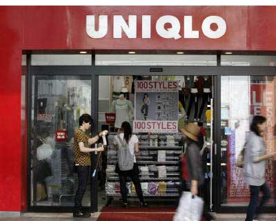 <b><p>People walk past Fast Retailing's Uniqlo store in Tokyo.</b>