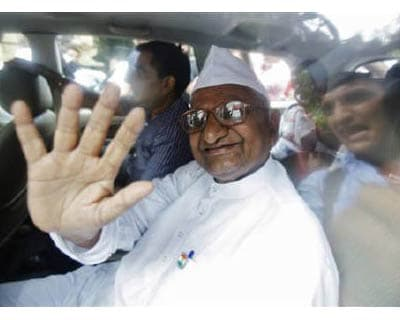"""<p><b>Veteran social activist Anna Hazare waves from a car after being detained by police in New Delhi</b></p><p>Police arrested anti-corruption campaigner Anna Hazare on Tuesday, just hours before he was due to begin a fast-unto-death, as the beleaguered government cracked down on a self-styled Gandhian activist agitating for a new """"freedom"""" struggle.</p><p>At least 1,200 followers of the 74-year-old Anna Hazare were also detained, signalling a hardline stance from Prime Minister Manmohan Singh against anti-government protests, a gamble that risks a wider backlash against the ruling Congress party.</p><p>Dressed in his trademark white shirt, white cap and spectacles in the style of independence leader Mahatma Gandhi, Hazare was driven away in a car by  plainclothes police, waving to hundreds of supporters outside his residence in New Delhi.</p><p>His followers later said he had begun his fast.</p>"""