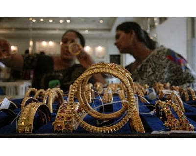 <p><b>Customers look at gold bangles inside a jewellery shop in Hyderabad</b> 