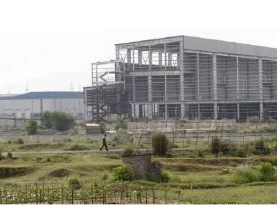 <p><b>File photo of a security guard outside the closed Tata Motors Nano car factory in Singur</b></p><p>Tata Motors, the auto arm of the iconic Tata group, said it will challenge in court a government decision to reclaim land in Singur, another instance of conflict over land that is the biggest block for rapid growth in India.</p><p>Tata Motors, India&#39;s top vehicle maker, abandoned plans in 2008 to build a plant on the land to manufacture what it says is the world&#39;s cheapest car, the Nano, in West Bengal after violent protests by farmers.</p><p>Returning the land to farmers was a central point of the campaign by the populist Trinamool Congress party during elections in the state in April, which saw voters throw out a three-decade old communist government. Trinamool is the largest ally of the Congress party.</p><p>Debasis Ray, a Mumbai-based spokesman for Tata Motors said on Wednesday the firm would contest the decision by the local government in the High Court in Kolkata, but