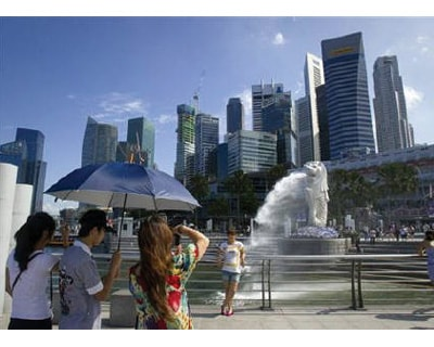 <p><b>A tourist poses for a photo in front of the Merlion, a mascot of Singapore, and the financial district skyline in Singapore </b>