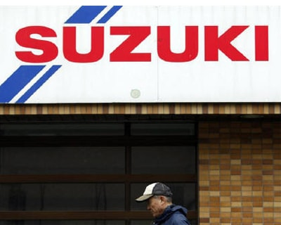 <p><b>A man walks past a Suzuki Motor car dealer shop in Tokyo </b>