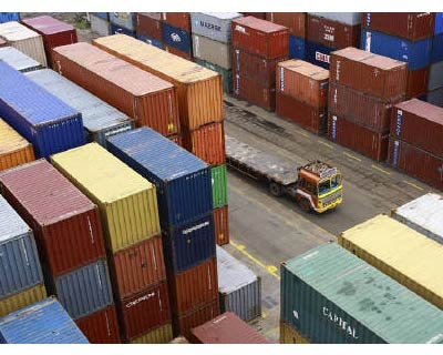 <p><b>A truck passes shipping containers stacked at the Container Terminal at the Cochin Port</b>