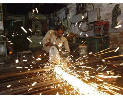 <p><b>An employee works inside a metal workshop in Kolkata</b>