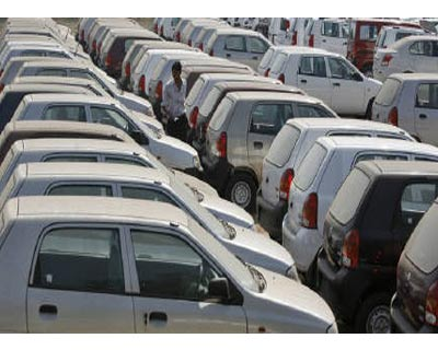 <p><b>An employee walks through parked cars at Maruti Suzuki&#39;s stockyard on the outskirts of Ahmedabad</b>