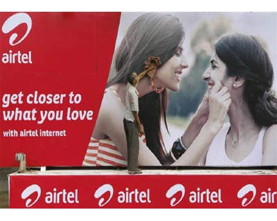 <p><b>A labourer cleans a Bharti Airtel advertisement billboard installed on a truck in Kolkata</b>