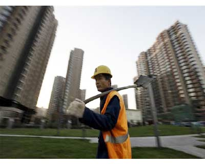 <p><b>A worker walks past apartment blocks under construction in Beijing</b>
