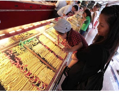 <p><b>A woman holds her son while looking at gold chains in a gold shop at Bangkok's Chinatown</b>