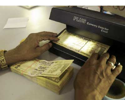 <p><b>A cashier checks currency notes inside a bank in Agartala, capital of Tripura</b>