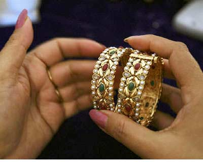 a customer selects one-carat gold bangles during an exhibition in jammu