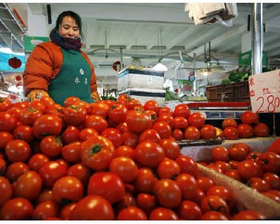 <p><b>A vendor stands next to tomatoes at a local market in Shanghai</b>