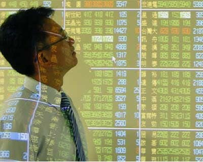 <p><b>A man walks past a display showing stock market prices inside a bank in Taipei</b>