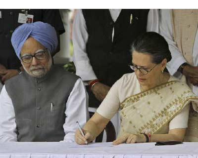 </p><b>Congress party president Sonia Gandhi watched by Prime Minister Manmohan Singh fills nomination papers seeking to retain her post as the party chief at her residence in New Delhi</b>