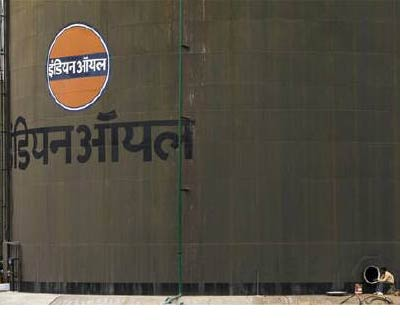 <p><b>A worker sits beside an oil tank at a storage facility of an oil company on the outskirts of New Delhi</b>