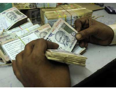 <p><b>An employee counts currency notes at a cash counter inside a bank in Agartala, capital of Tripura</b>