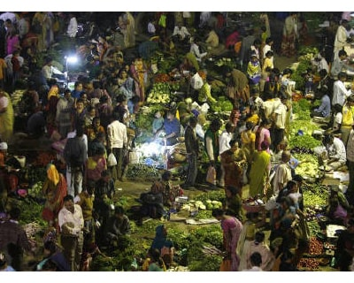 <p><b>Customers shop at an open air evening vegetable and fruit market in Ahmedabad </b>