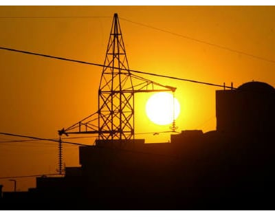 <p><b>Sun sets behind a power tower near a building in New Delhi.</b>