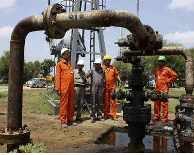 """<p><b>Engineers stand inside an oil field in Gujarat</b> </p><p> Oil ministry of India brushed off a report it could bar companies with funding from China, Pakistan or Bangladesh from bidding for exploration licences as relations with these neighbours remain sensitive. </p><p> """"We have no such information,"""" Oil Secretary S Sundareshan told reporters, when asked about a report in Mint that the government had barred such companies from participating after a request from the defence ministry. </p><p> Neighbouring economic powerhouses India and China have repeatedly sparred diplomatically over last two years despite bilateral trade that has grown 30-fold since 2000. </p><p> Last week, Manmohan Singh warned that China, our main rival for regional resources, was seeking to expand its influence in South Asia at expense of India. </p><p> India aims to launch the next round of licensing for oil and gas blocks in the third quarter, the oil ministry said in June. </p>"""