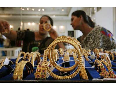 <p><b>Customers look at gold bangles inside a jewellery shop in Hyderabad</b> </p><p> India gold futures struck a fresh record high of Rs 19,250 per 10 grams on Wednesday afternoon, tracking gains in overseas markets, breaching the earlier peak of Rs 19,230 struck on Tuesday. </p><p> The contract trading ended at Rs 19,222 at market close. </p>