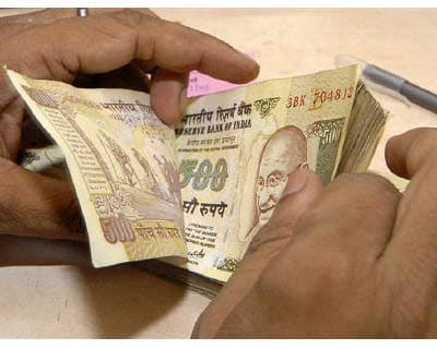 <p><b>A cashier counts currency notes inside a bank in Lucknow</b>