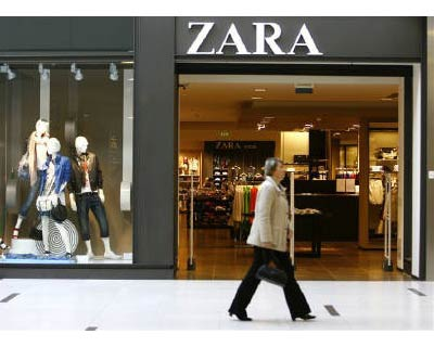 <p><b>A woman walks pass a Zara shop in Riga Plaza shopping center in Riga </b>
