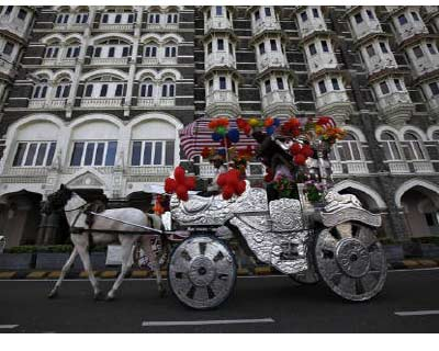 <p><b>A horse-drawn carriage carrying tourists moves past the Taj Mahal hotel in Mumbai</b>