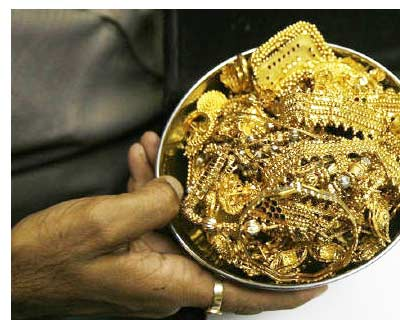<p><b>A trader holds gold jewellery at a shop in Mumbai</b>