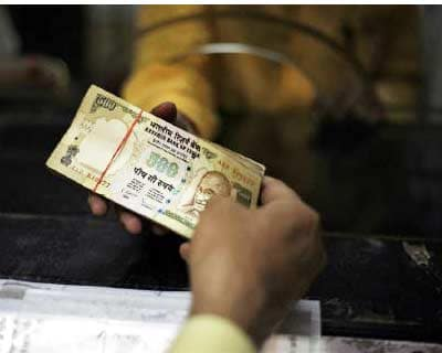 <p><b>A man deposits his money in a bank in Amritsar</b>
