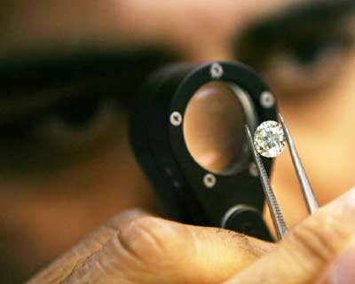 <p><b>A diamond businessmen desmonstrates a process at a diamond cutting and polishing factory in Surat</b>