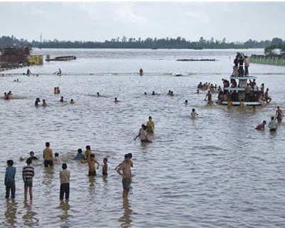 <p><b>Local residents stand on a flooded road after heavy monsoon rains at Moradabad in Uttar Pradesh</b>