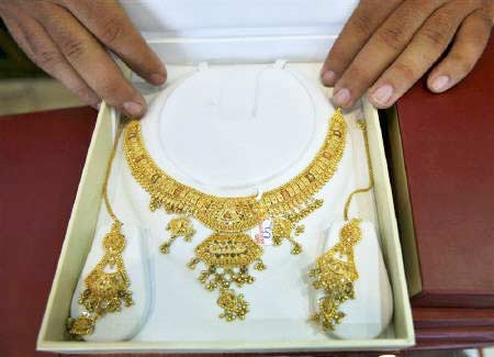 <p><b>A shopkeeper displays gold jewellery inside his showroom in Jammu</b>