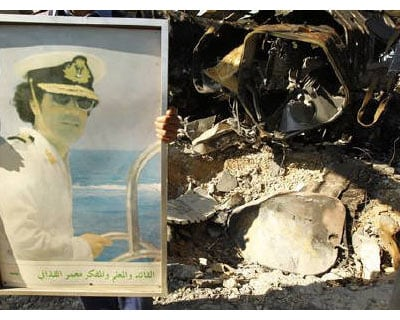<p><b>A Libyan holds a portrait of Libya&#39;s leader Muammar Gaddafi, while standing beside a crater caused by coalition air strikes, at a naval military facility in eastern Tripoli</b></p><p>Western powers attacking Libya will end up in the dustbin of history, Muammar Gaddafi said as his troops held back rebels despite 4 nights of air strikes.</p><p>While Western air power has grounded Gaddafi&#39;s warplanes and pushed back his forces from the brink of rebel stronghold Benghazi, disorganised and poorly equipped insurgents have failed to capitalise on the ground and remain pinned down.</p><p>The rebels have been unable to dislodge Gaddafi&#39;s forces from the key junction of Ajdabiyah in the east, while government tanks are besieging the last big rebel hold-out of Misrata. There is big risk of stalemate on the ground, analysts say.</p>