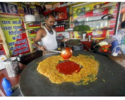 <p><b>A cook prepares local cuisine, Pav Bhaji, at a beachside restaurant in Mumbai</b>