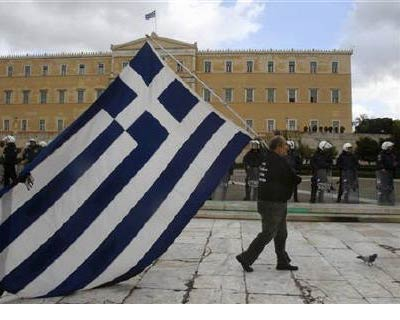 <p><b>A striker parades with a huge Greek flag in front of riot police guarding the parliament during a demonstration in central Athens </b>