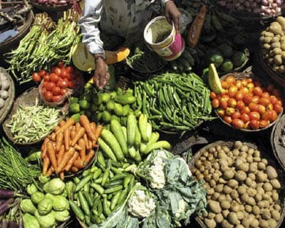 <p><b>A vendor sprays water on vegetables to keep them fresh at a market in Siliguri</b>
