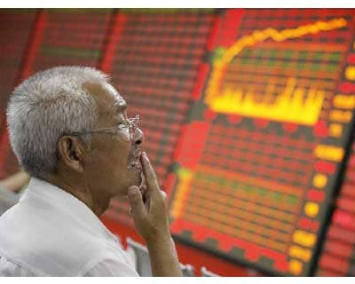 <p><b>An investor looks at stock information in front of an electronic board at a brokerage house in Huaibei, Anhui province</b>