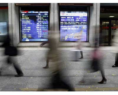 <p><b>People walk past a stock quotation board outside a brokerage in Tokyo</b>